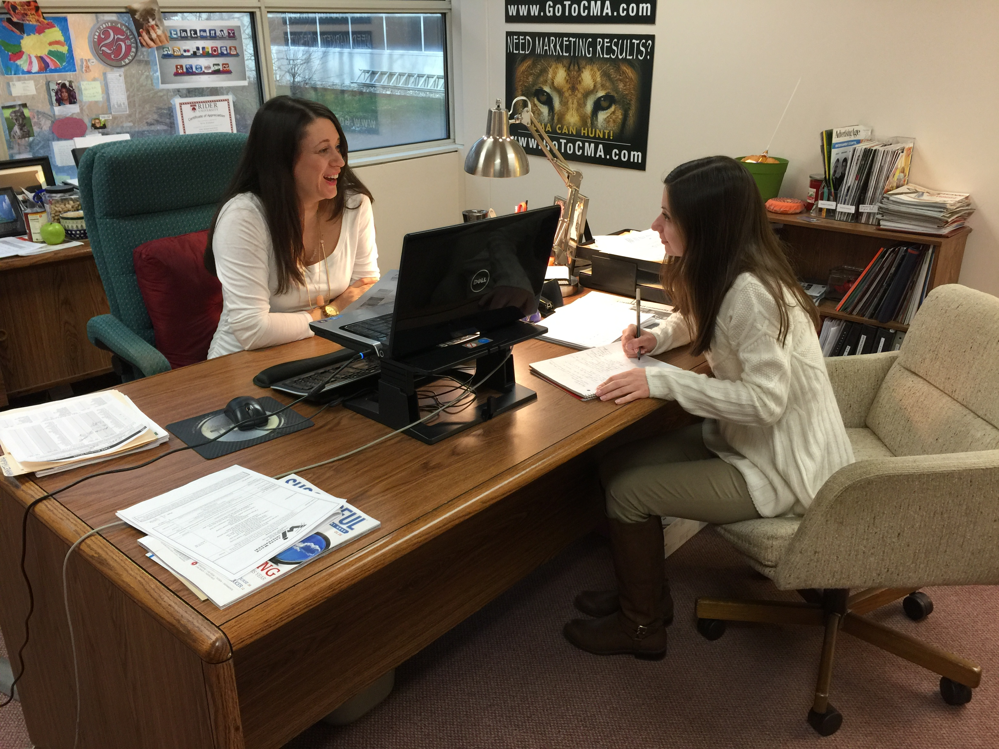 Alexandra Perrine, a Rider University marketing major from West Windsor, works with Erin Klebaur, director of marketing services, as she reports her findings after doing website evaluations as part of her internship at Creative Marketing Alliance.