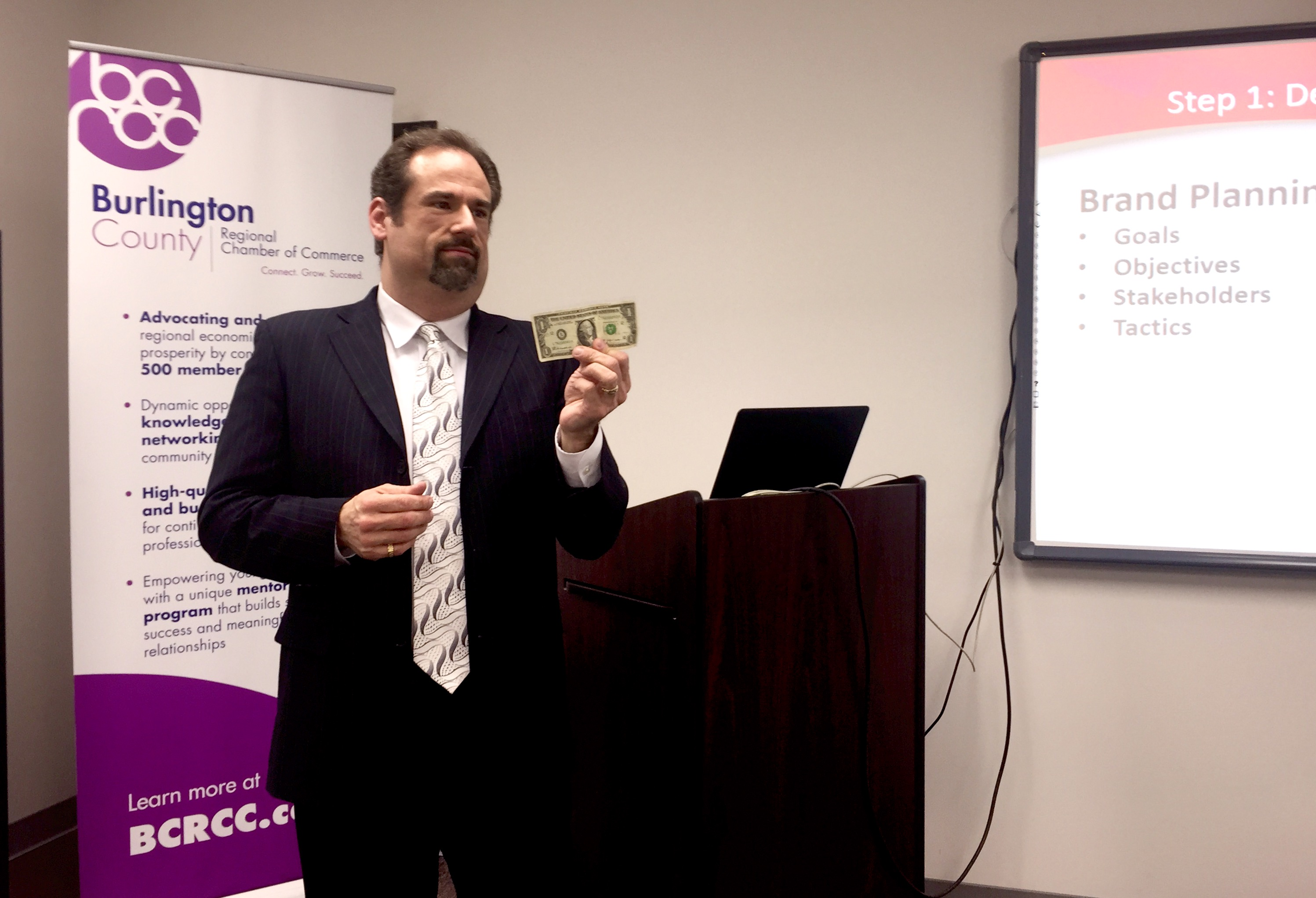 Kenneth Hitchner, public relations and social media director at Creative Marketing Alliance, holds up a dollar bill as an example of branding.