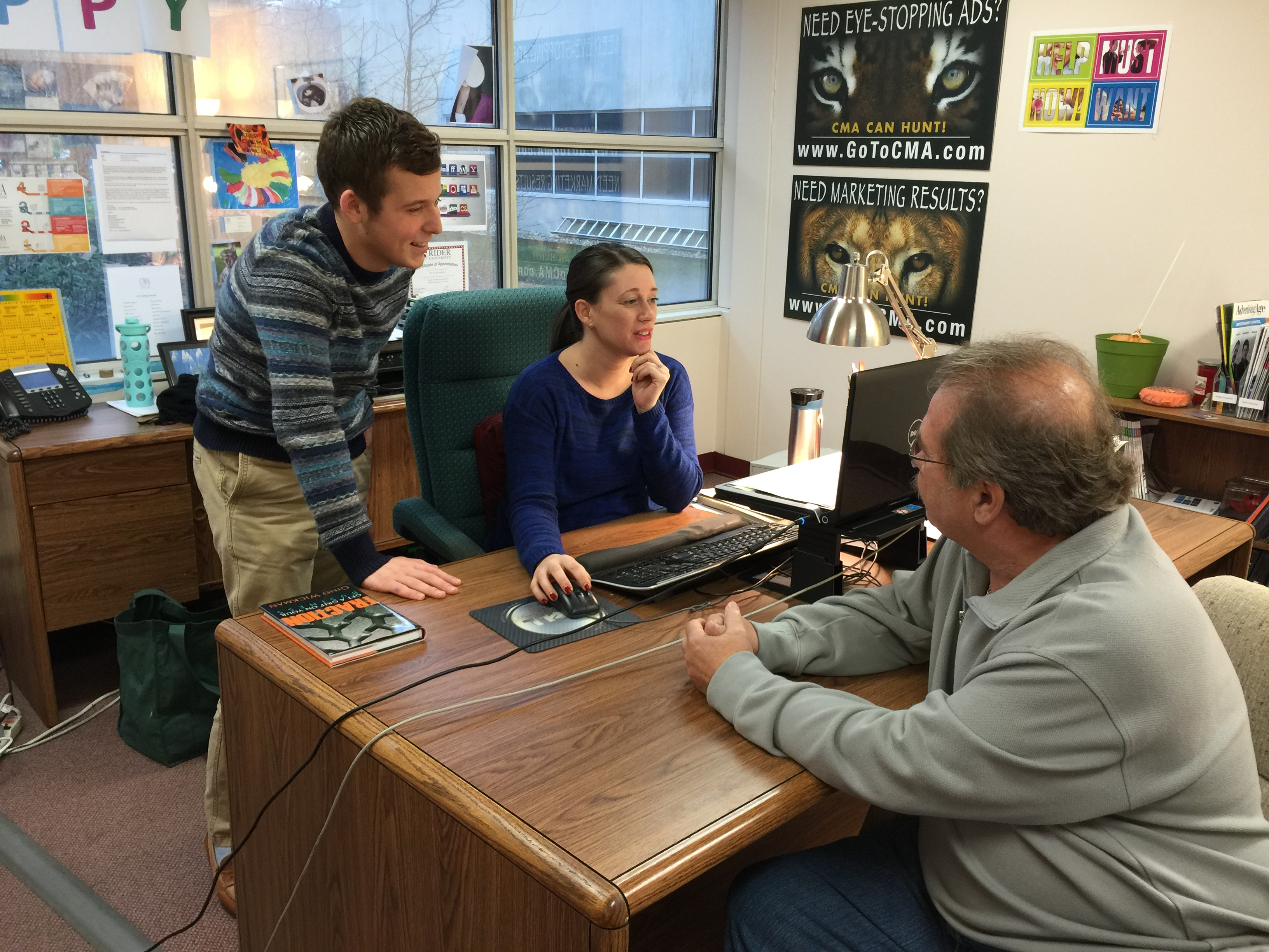 Kevin Grunder, a public relations major at Rider University who lives in Linden, works with Erin Klebaur, director of marketing services, and Jeff Barnhart, CEO and president, as he gets ready to present his ideas for the CMA blog to the management team as part of his internship at Creative Marketing Alliance.