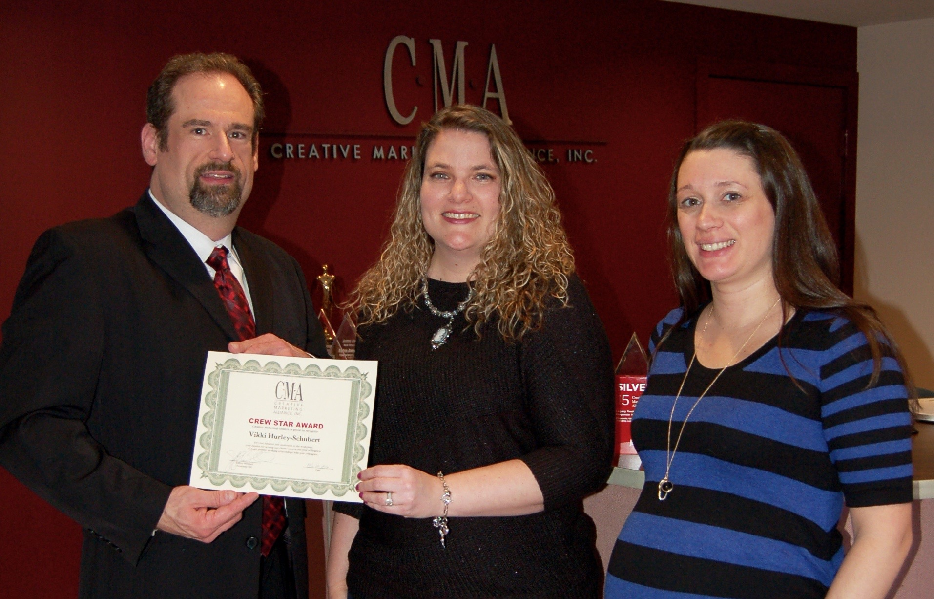 Kenneth Hitchner, public relations and social media director and fourth quarter Crew Star presents Victoria Hurley-Schubert, public relations account executive with the Crew Star award for the first quarter with Erin Klebaur, director of marketing services.
